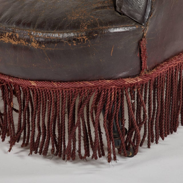 Early 20th century French leather slipper arm chair with fringe.