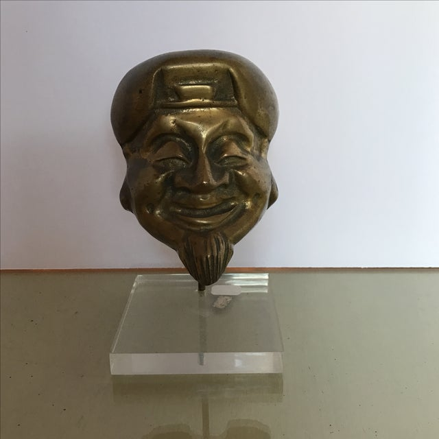 This is a Mid-Century bronze Buddha head mounted on a lucite base. It shows wear consistent with its age.