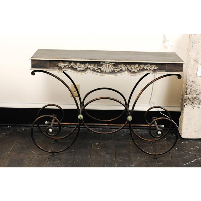 A French vintage baker's table with painted wood top and iron base. This whimsical French table features a painted wood...