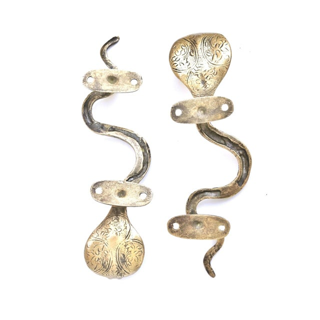 A pair of antiqued brass cobra door handles or cabinet pulls. Hollywood Regency in style, with intricate carving...