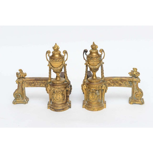 Louis XV gilt bronze chenets. Illustrated with flame finials on top of urns and balustrade. Garland draped with leafage....