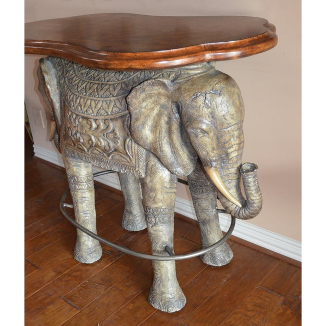 """Two-headed elephant bar has amazing detailing (on both sides) and a foot rail around the base. Measures 42"""" high. The top..."""