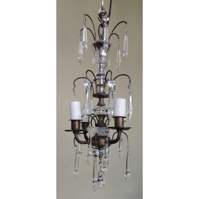 This chandelier was made in the early-20th century. The brass structure of this piece features thinner rounded arms that...