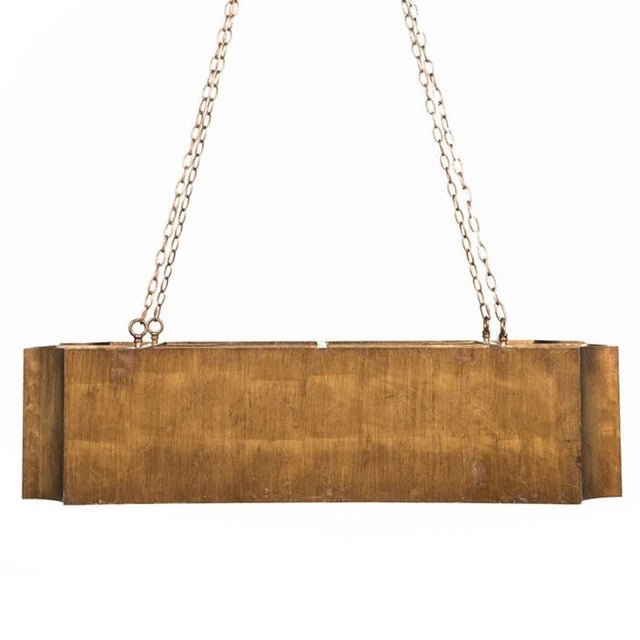 This oversized rectangular kitchen island pendant contains an antique gold outer finish and gold backing on the inside....