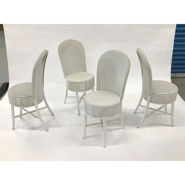 Set of 4 charming chairs by Lloyd Loom, circa early 1950s. Hoop back form with round pill-shaped seat. Woven with wrapped...