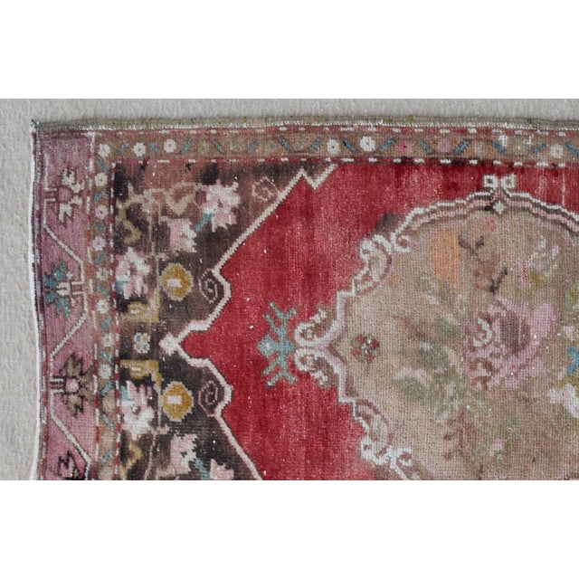 Hand-knotted Turkish wool accent rug in wonderful muted reds, pinks and cream hues. Some wear consistent with age/use.