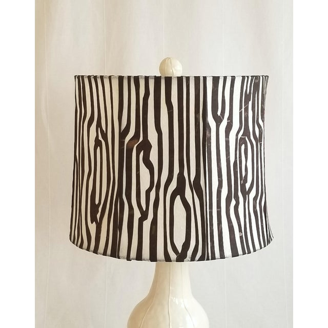 Tall, white VIT ceramics table lamp is paired with a unique, handmade rice paper shade by Jil Smith of Insatiable Studios....