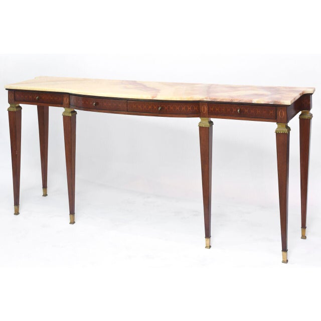 The onxy top over a frieze inlaid in geometric form with four drawers, over square tapering legs headed with bronze mounts...
