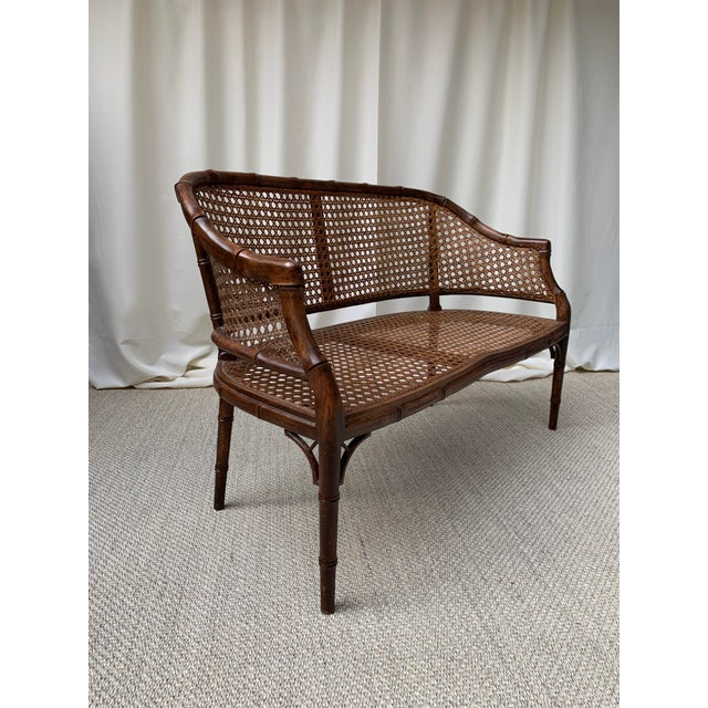 A signature faux bamboo settee loveseat features a cane back and cane seat in perfect original condition. The fretwork and...