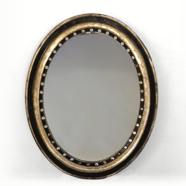 Irish oval mirror with moulded parcel-gilded and ebonized frame, applied with mirrored glass facets and cross-hatch...