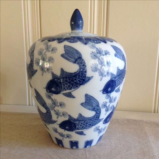 Blue-and-white ceramic Asian ginger jar or vase embellished with a Chinoiserie-style fish and leaf motif.