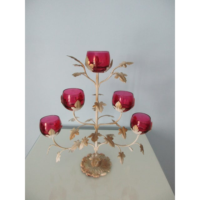 This beautiful candelabra has five rose colored bowls, perfect for small votive or tea light candles. The metal body of...