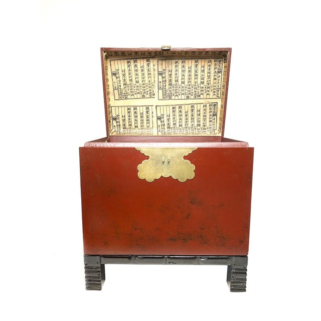 Vintage 1940s Chinese red lacquer wooden trunk with stunning brass butterfly latch and ming style legs. The box portion is...