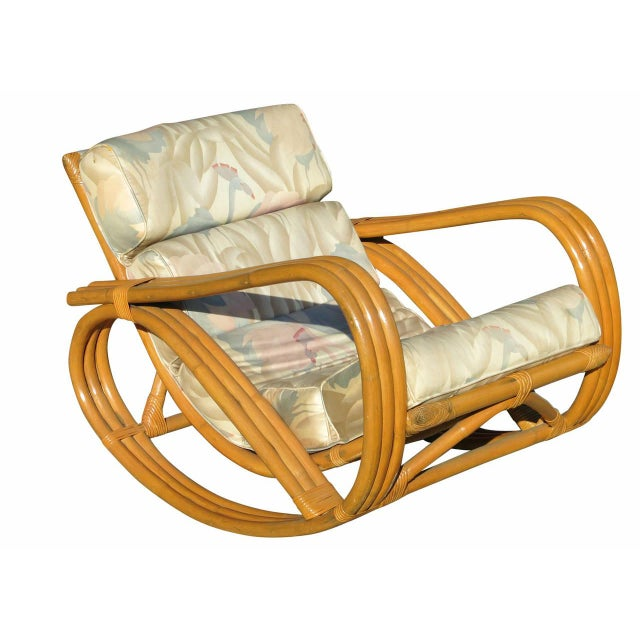 A rare Paul Frankl inspired three-strand pretzel arm rattan rocking chair with matching ottoman. This chair features a...