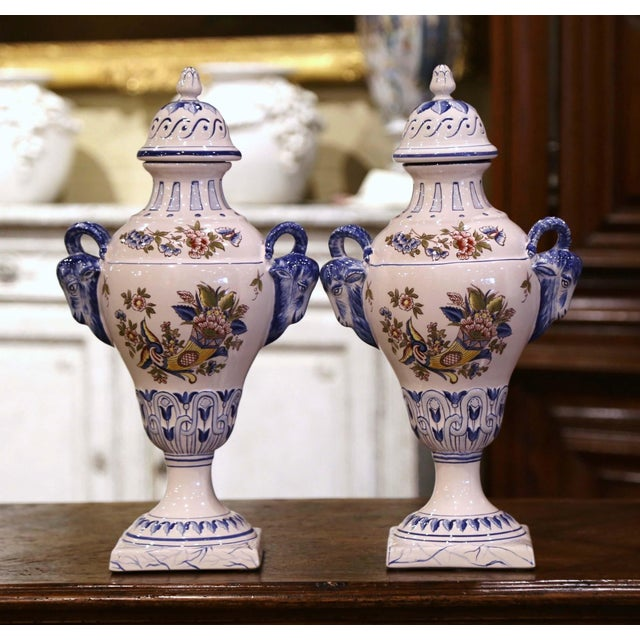 These elegant, antique urns were created in Luneville, France, circa 1970. The tall ceramic vases stand on square bases...
