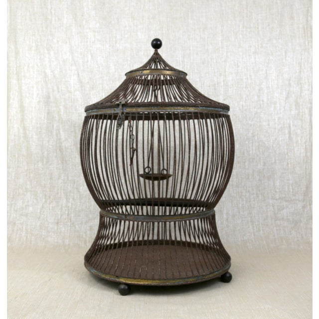 Hand-wrought iron with copper trim birdcage. HEAVY & HUGE, round birdcage weighs over 25 pounds. Includes perch and...