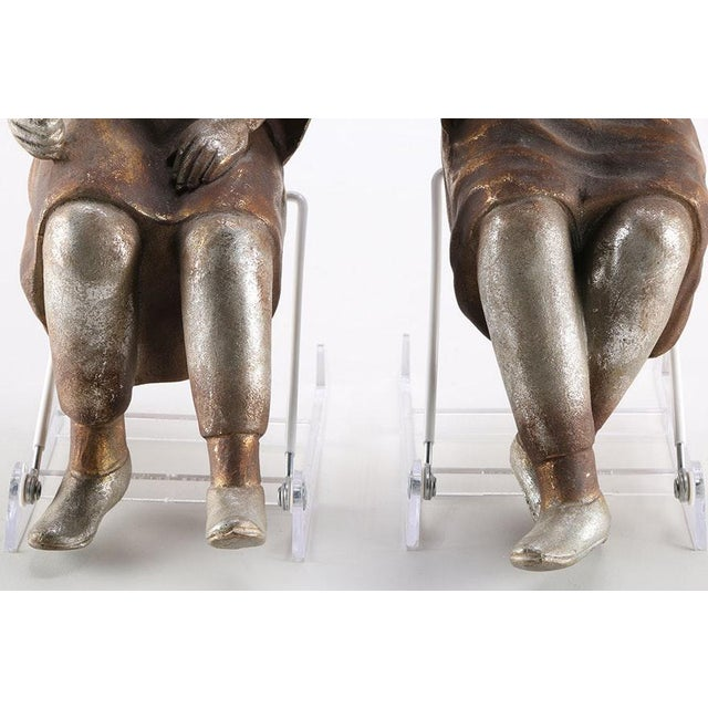 A pair of silver tone and gold tone figurines depicting seated men in traditional Asian dress. One figure, with crossed...