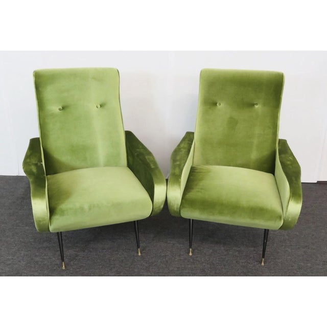This stylishl sculpted pair of 1950s Italian modern armchairs feature tapered legs with brass tipped feet. With vibrant...
