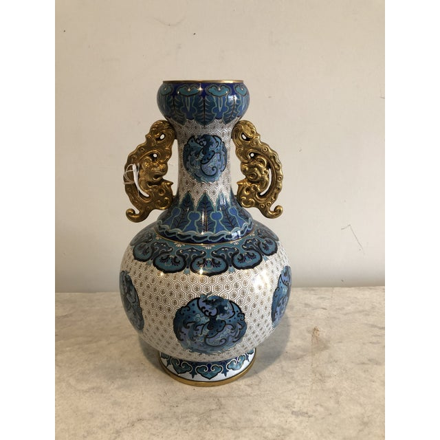 In a palette of blue, turquoise, navy, white and gold, this Chinoiserie vase is enameled in cloisonné style. The vase is...