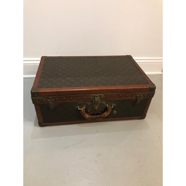 French, 20th century. A Louis Vuitton suitcase with a monogram canvas exterior, leather and brass-bound (all rivets and...