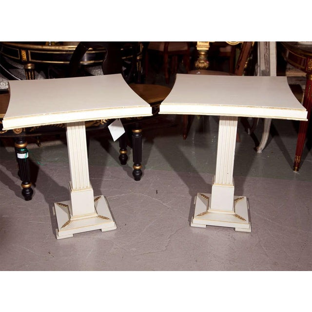 A pair of square top painted and parcel-gilt tables by Grosfeld House, circa 1950s, supported by a single fluted pedestal,...