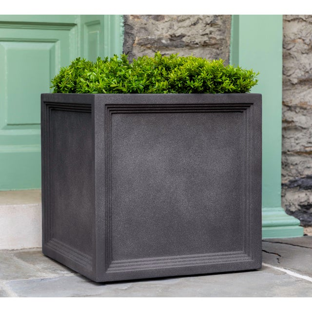 A planter of Fiber Clay Composite with a concrete finish, featuring stepped, inset sides. Available in multiple sizes....