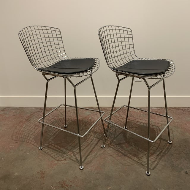 This pair of chrome Bertoia bar stools by Knoll have never been used and come with black leather seat cushions.