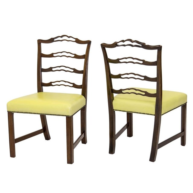Vintage pair of traditional Chippendale-style mahogany ladderback side chairs with yellow vinyl seats and brass nailhead...