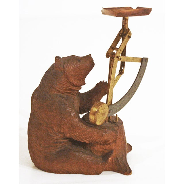 A whimsical carved Black Forest bear holding a postal scale which sits on a carved tree stump. Late 19th Century Germany