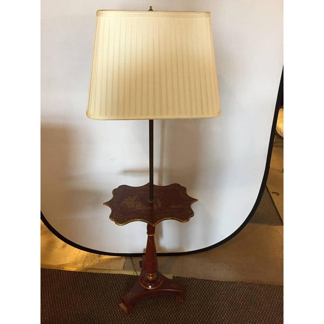 A red chinoriserie decorated table lamp with custom shade. On a tripod base leading to a paint decorated column pedestal...