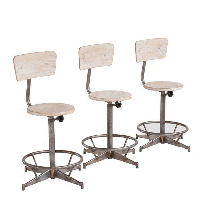 A light wood and metal adjustable swivel high chair(6 available). seat height adjusts from 20-28 high