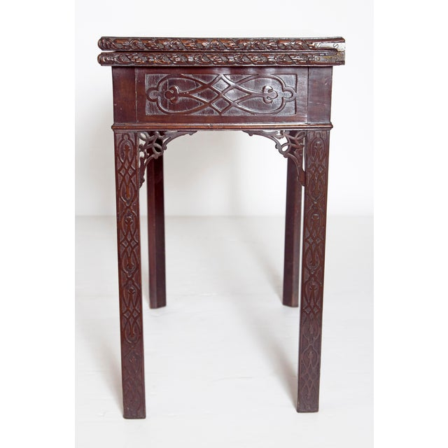 A flip-top George III card table with a carved rosette edge above a blind fretwork frieze decoration with pierced bracket...