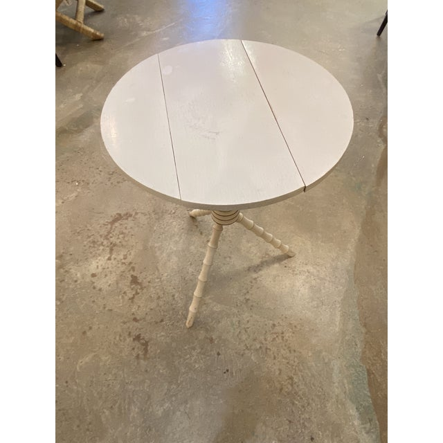 Beautiful little creamy white round table made in Maine 1800's. Makers label on the underneath. Dark gold painted accents....