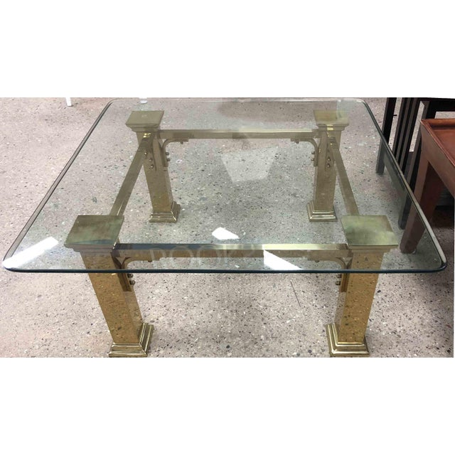 This stunning mid-century coffee table features heavy solid brass Art Deco inspired columnated leg base. The table top is...
