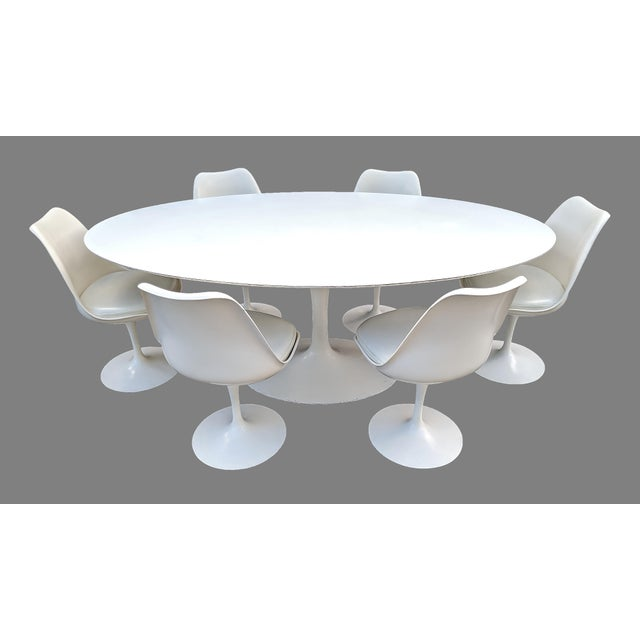 1980's Eero Saarinen for Knoll dining set with oval tulip table and 6 tulip chairs which swivel. Chairs are dated 1986....
