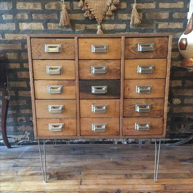 A charming card catalog that has been recently restored and set on four hairpin legs. Featuring 15 drawers with a generous...