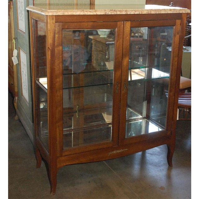 A well proportioned two door display cabinet with a full shelf at the mid-section. The cabinet has an interior mirrored...