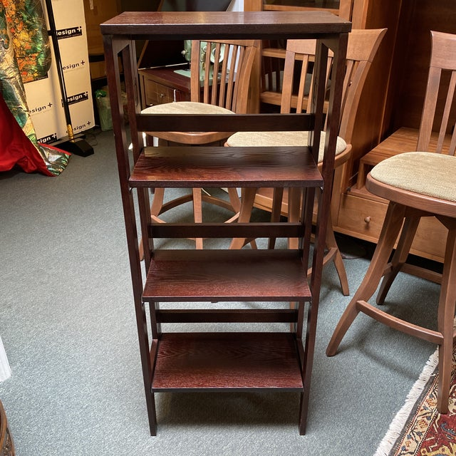 Design Plus Gallery presents a folding bookcase. A dark rich finish is the framework for your collection of books or...