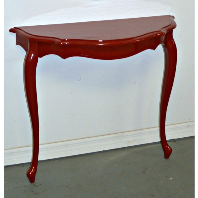 Demilune console refinished in purple-red. The wooden console has two legs and must be fixed to the wall with hardware.