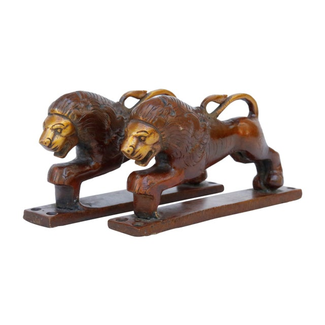 A pair of red brass lion door handles or cabinet pulls. Hollywood Regency in style, with intricate carving throughout....