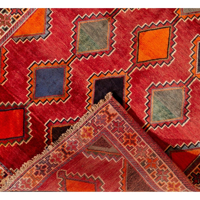 Beautiful Vintage Persian Rug, with a red field, orange and blue accents in an allover geometric design. This rug measures...