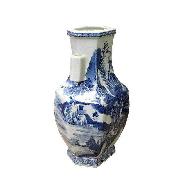 This is a Chinese decorative porcelain vase in Blue and White color finish. The theme is oriental mountain tree scenery...
