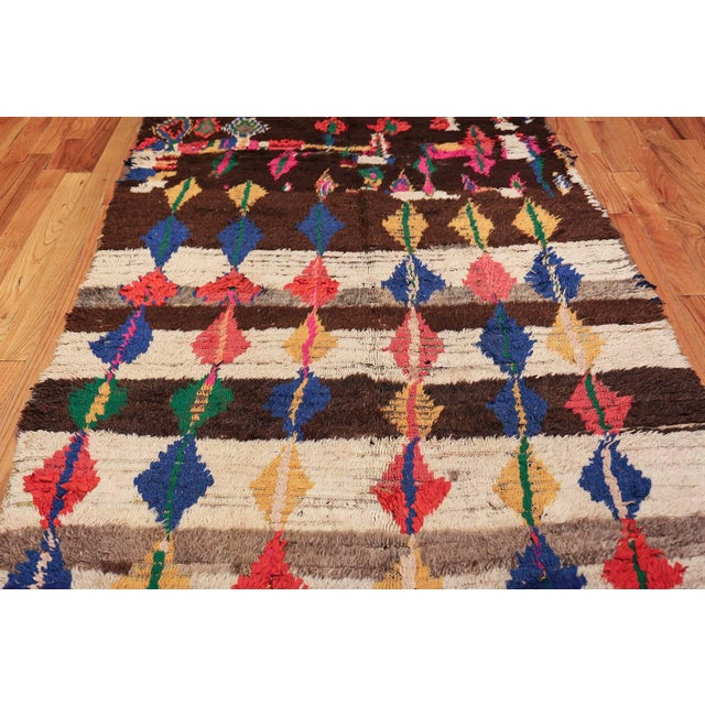 This vintage Moroccan rug features a series of colorful rhomboid figures linked in an abstract all-over pattern. Vintage...