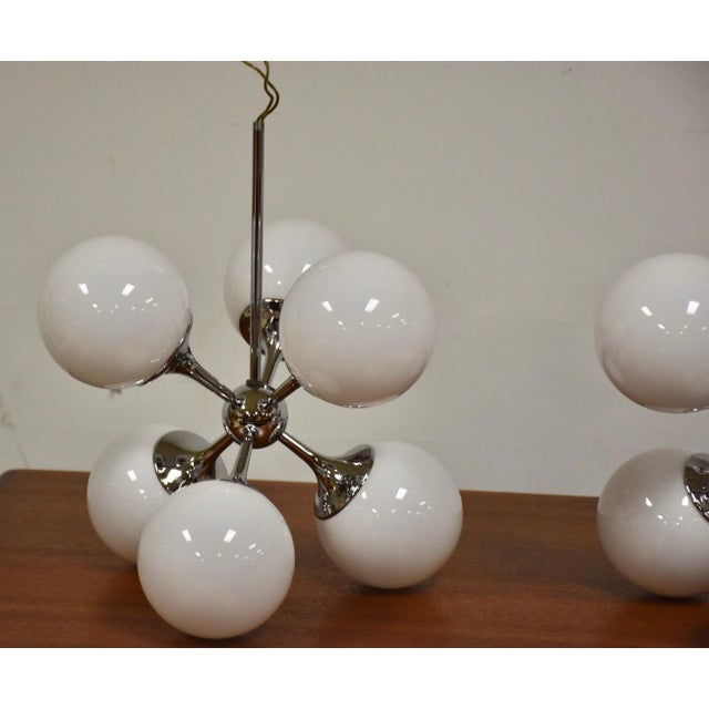 A rare set of three chrome sputnik light fixture chandeliers with white glass orb shades made by Lightolier. These would...