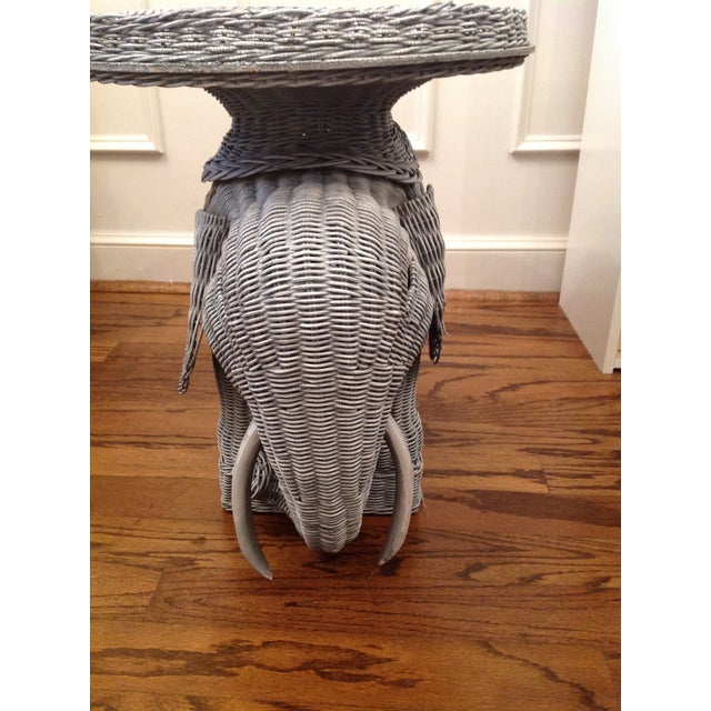 Vintage wicker elephant table. It has been painted a gray. Needs a fresh coat of paint. Has a few loose pieces of wicker...