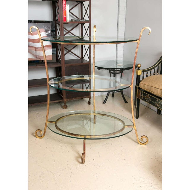 Three-tier glass and gilt metal etagere stand. Warm toned gilt metal curved legs that connect three circular bases that...