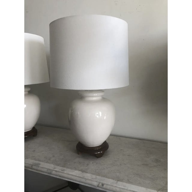 Pair of mid-century white ceramic lamps w/wood base and mew white linen drum shades. Perfect side table lamps for bedside...