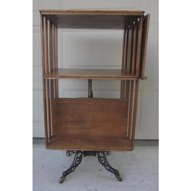 Offered is an antique revolving oak library or lawyers bookcase with a decorative wrought iron base on wheels. It's in the...