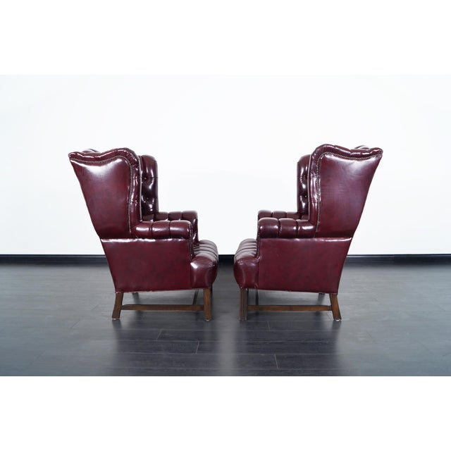 "Pair of stunning burgundy leather tufted wingback chairs. Ottoman comes included. Ottoman: 32""W x 24.75""D x 15.25""H."