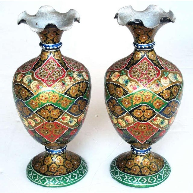 A vibrant and unusual pair of Kashmiri papier mache polychromed urns; each with ruffled lip above an ovoid body over a...